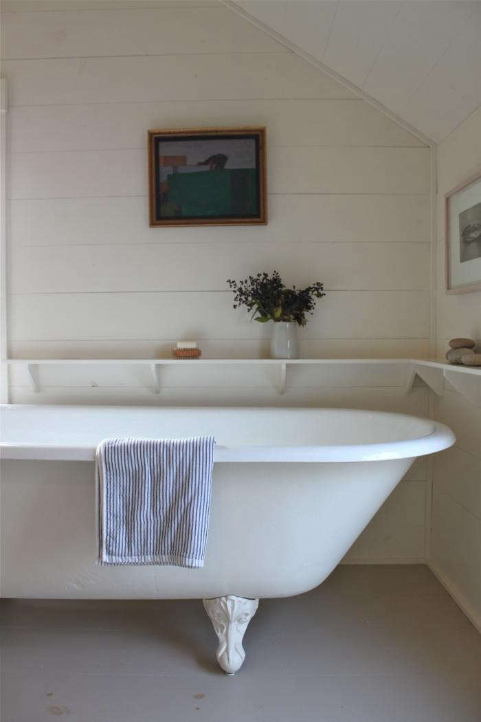 In the bathroom at Harbor Cottage in Maine (see A Cottage Reborn in Rural Maine), architect Sheila Narusawa installed a running shelf that not only creates a cozy frame for the bath but also introduces useful storage.
