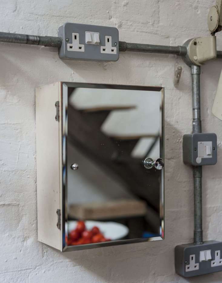 Surface-mounted galvanized steel conduit (for light switches and outlets) surrounds a medicine cabinet used for spice storage.
