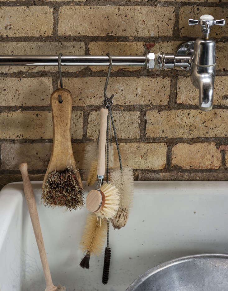 Scrub brushes hang from S-hooks on the sink's exposed piping.
