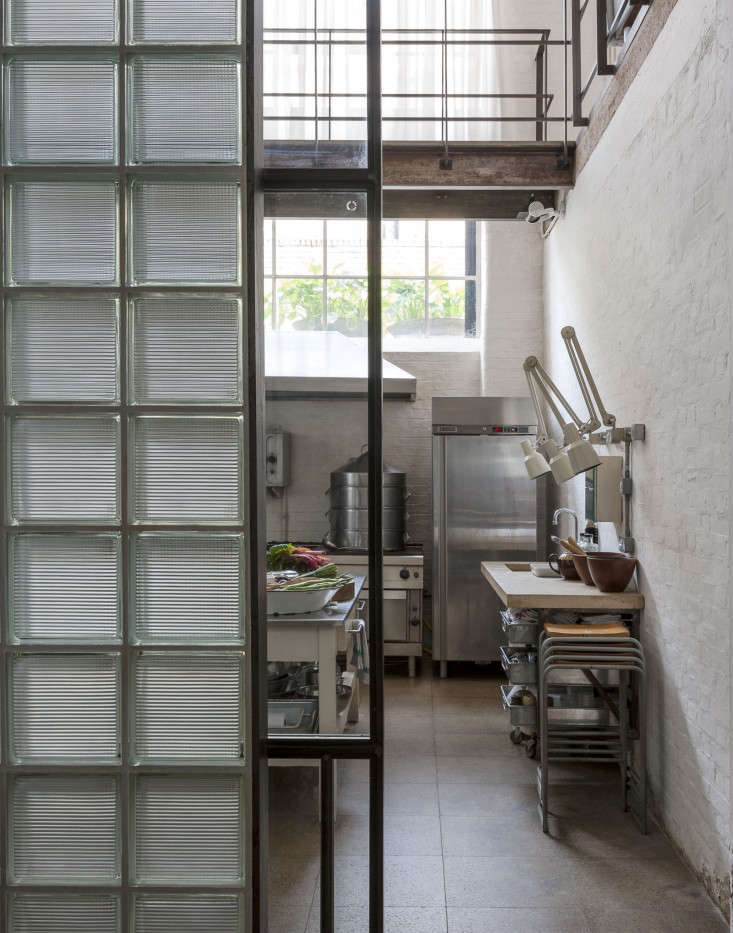 A steel-framed glass brick wall–a sign of the eighties–divides the kitchen from the bedroom area. It maximizes the light from the kitchen yet provides privacy.