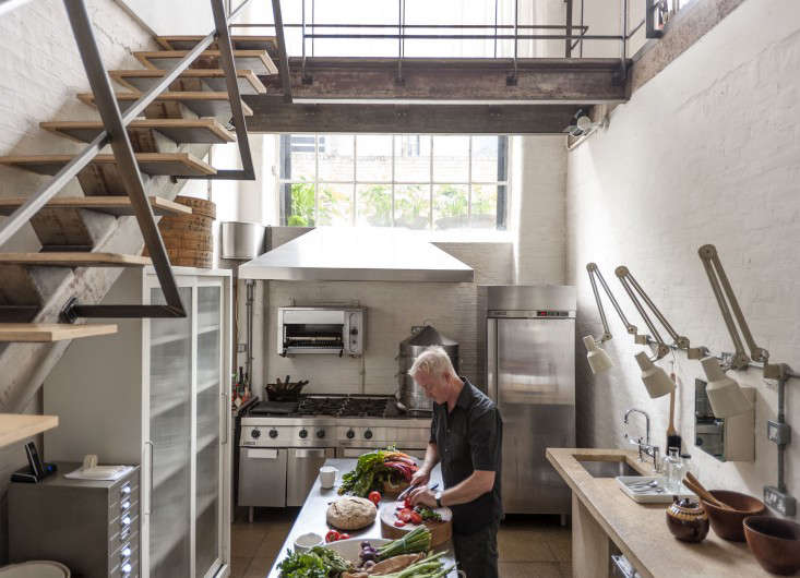 """Hendy at his worktable. The two-story loft is set in a converted industrial building in Hoxton and has a living room that overlooks the kitchen. """"When cooking, I can easily communicate with friends upstairs–and this saves the kitchen from actually being in the living area,"""" says Hendy. Note the cast concrete work counter and vintage Anglepoise hospital lights (""""£2.50 back in the day when no one valued industrial"""")."""