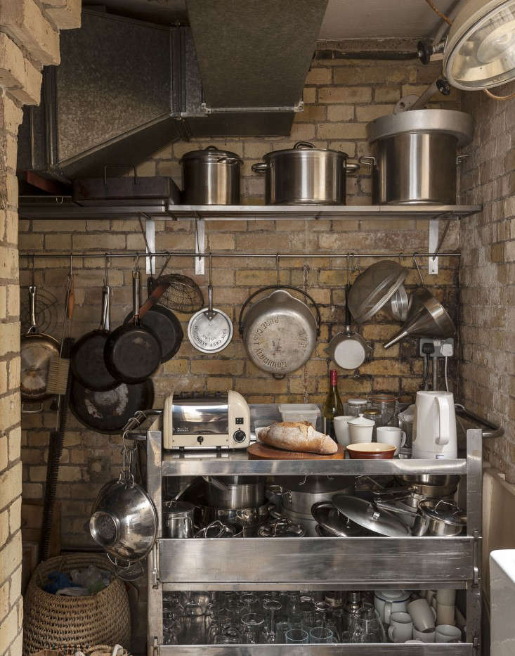 """A yellow brick-walled scullery off the kitchen is for storage and washing up; food staples are stored in an adjacent pantry. The stainless steel restaurant trolley holds, among other things, the electric tea kettle and toaster. A dentist's lamp, visible in the top right, lights the butler's sink. """"The scullery and pantry have gone out of fashion but I think they're of utmost importance,"""" says Hendy. """"Rip out all those fitted cupboards and have a walk-in area; it's much more efficient and if positioned correctly, food is kept properly cool."""""""