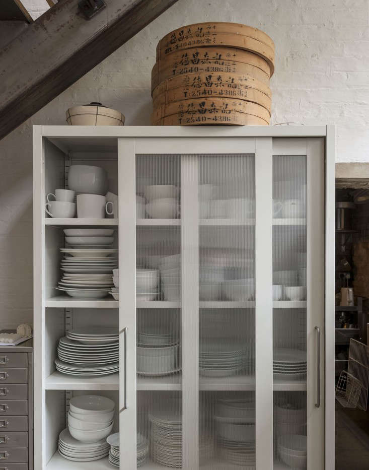 """A cabinet from Habitat holds Hendy's all-white dinnerware. """"Food always looks great on plain white. The food then does all the talking. I can't abide patterned plates."""""""