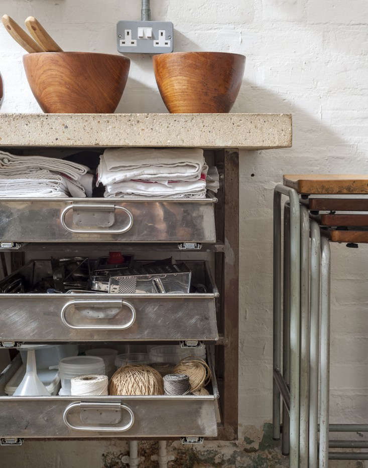 Under a concrete counter top, Hendy had a steel frame made to hold old steaming drawers from an oven. They're filled with his kitchen essentials, from dish towels to twine.