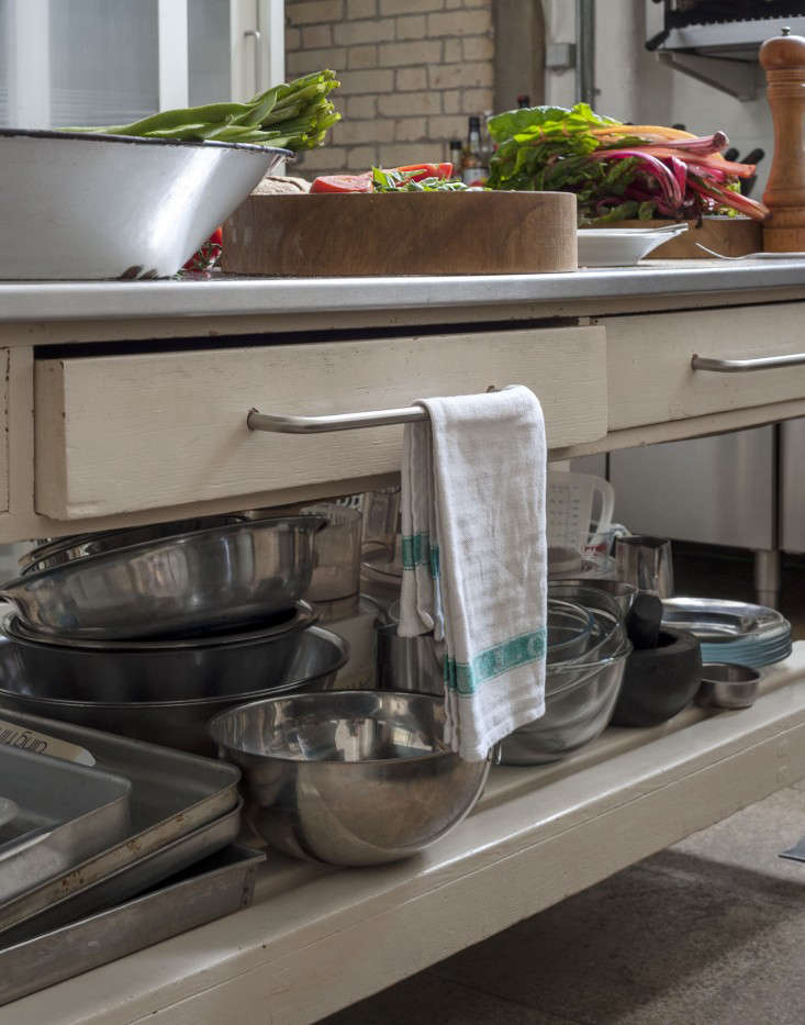 The worktable came from a school. Hendy added the stainless steel top (over crumbling melamine), painted the frame eggshell white, and added new handles.