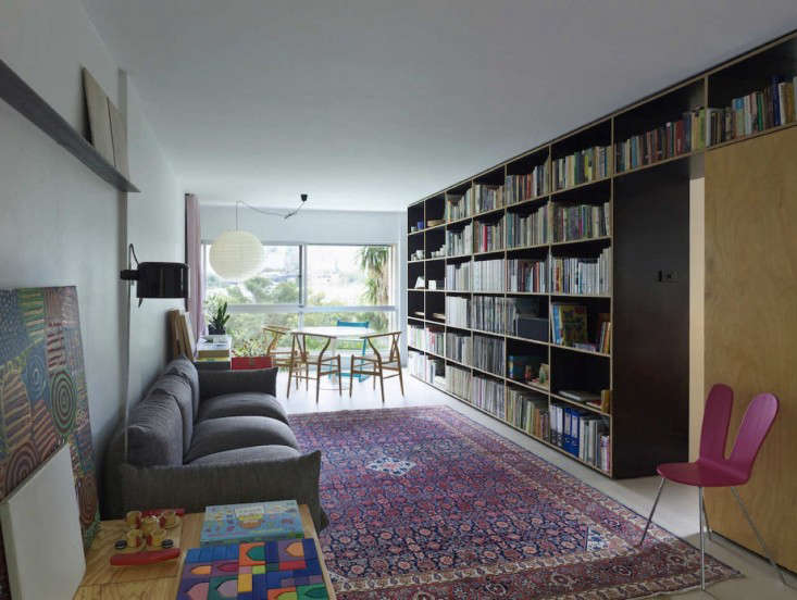 The shelves act like the apartment's spine, providing a structured backdrop for living.