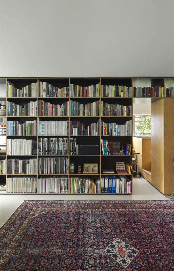 The key to Gill's success: a 23-foot-long, floor-to-ceiling shelving unit forms a dividing line down the core of the apartment. The kitchen, bathroom, and his daughter's room are on one side of the modular cabinet and the living area is on the other.