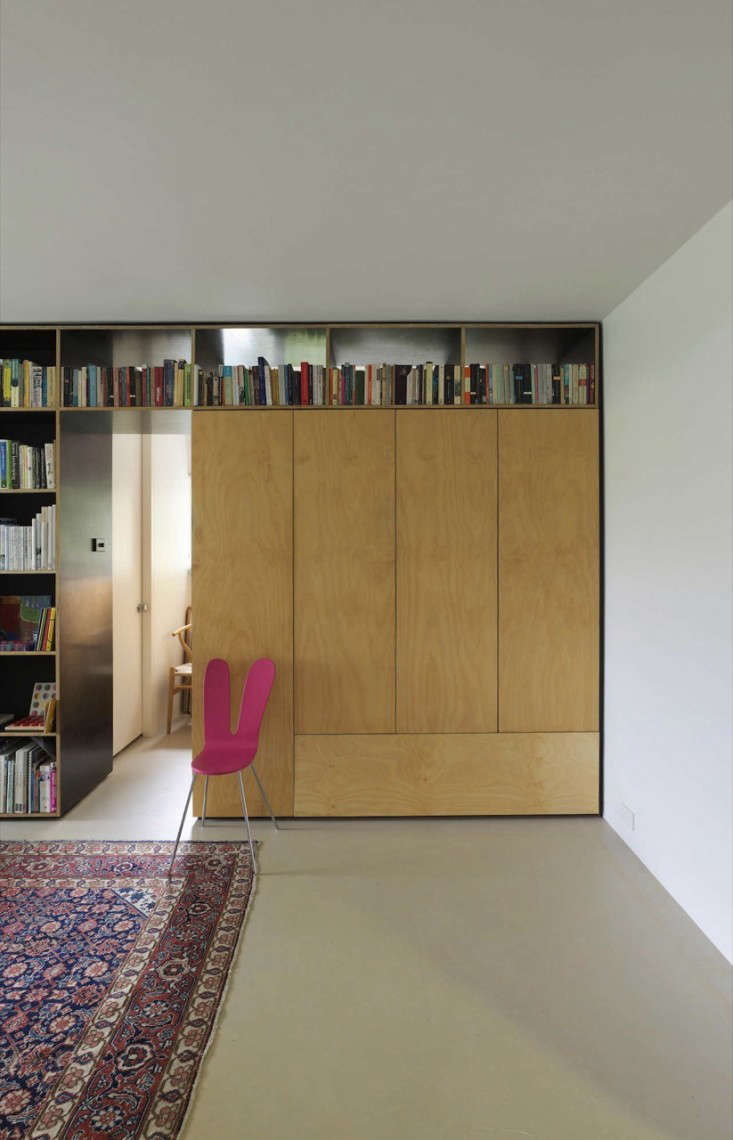 During the day, the master bed is hidden in the the plywood storage unit, giving the living area more usable space.
