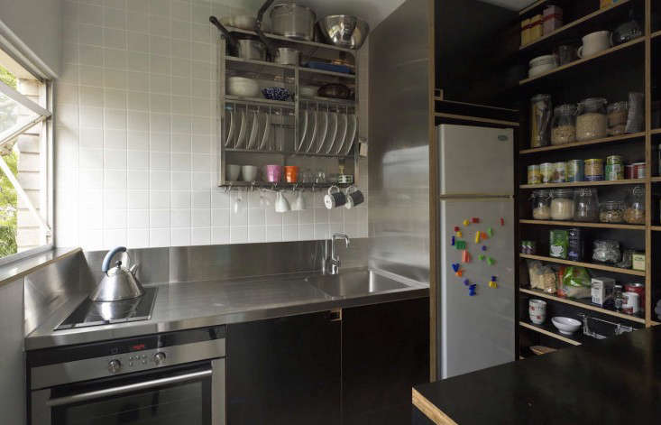 The compact black-and-white kitchen has a stainless steel counter that extends as a fridge frame. An Indian Stainless Steel Dish Rack on the tiled wall keeps surfaces clear.