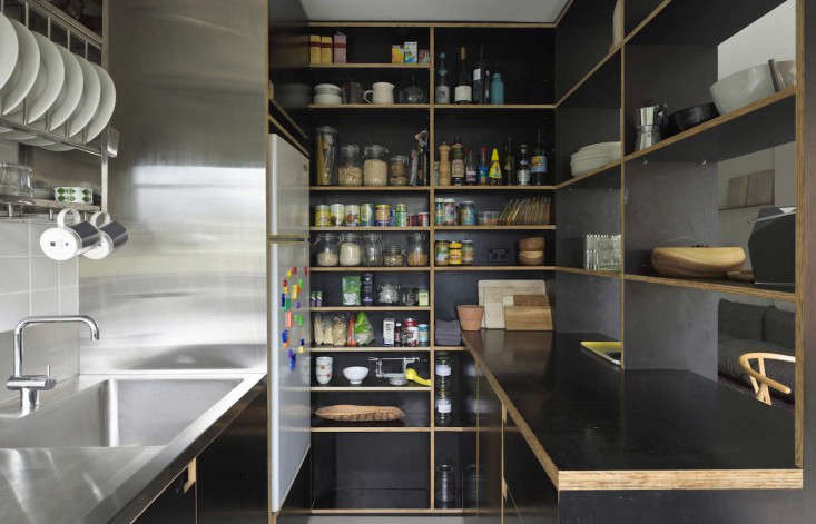 The black Formply shelves wrap around into the kitchen and become a counter with cabinets beneath.