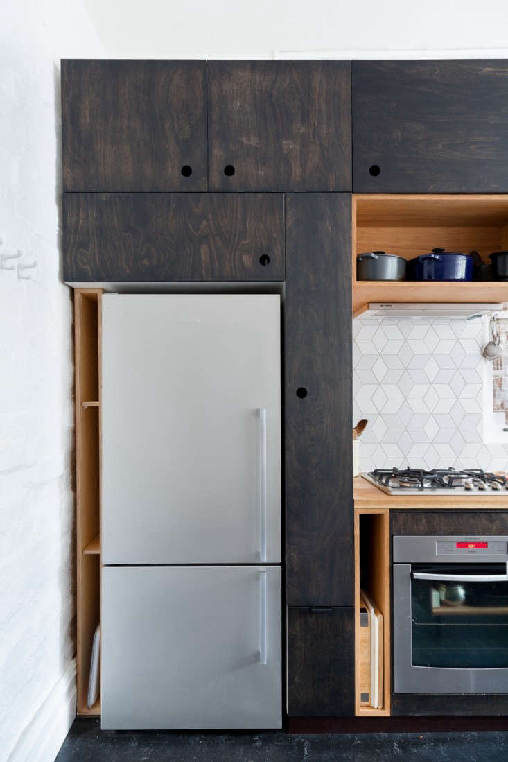 Most people would think the sliver of space between the refrigerator and the wall would be unusable, but in Trotter's hands, it becomes storage slots for cutting boards and oven pans.