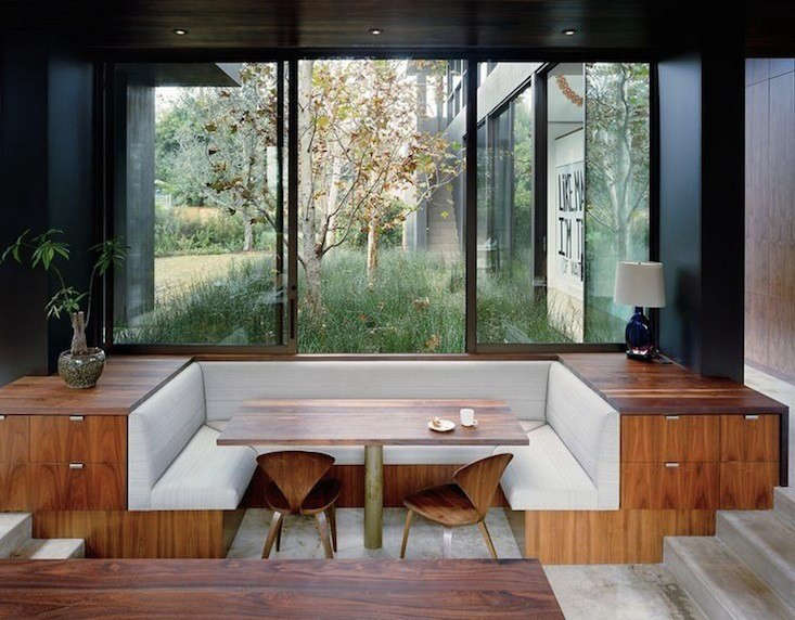 A built-in banquette with surrounding drawers overlooks a garden in Venice, California, by Marmol Radziner.