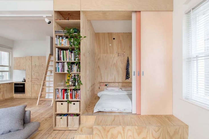 The plywood master bedroom incorporates built-in storage and a headboard that serves as a dividing wall between the master bedroom and the child's bedroom on the other side of the box. Photography by Lisbeth Grosman via Desire to Inspire.