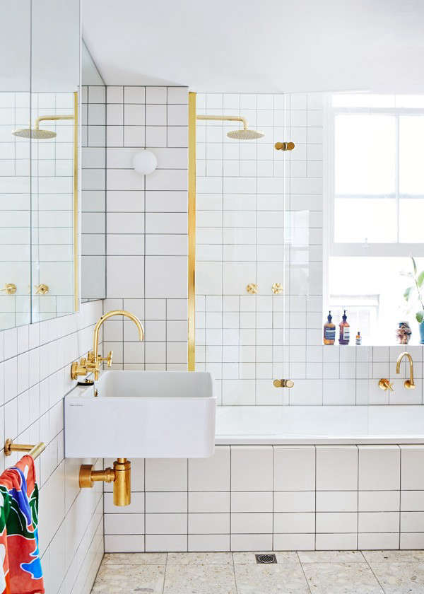 In the bathroom, Cousins created interesting tile patterns from simple white tiles and carried over the gold hardware from the kitchen.