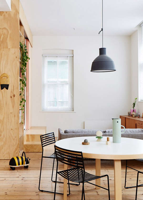 A black Unfold Pendant Lamp by Muuto hangs above the 91 Dining Table by Arkek. Straightforward blinds as window treatments help to maintain an unfussy aesthetic in the small apartment.