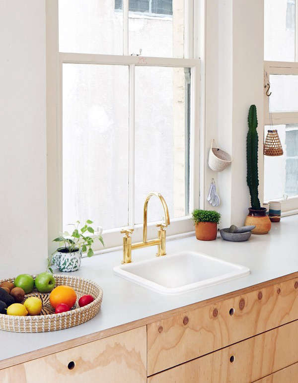 An electroplated gold faucet adds an element of glamor and surprise to the modest kitchen. In Steal This Look: The Modern Plywood Kitchen, Gold Faucet Edition, we show you how to recreate the kitchen. Like the cutout cabinet handles? See 10 Favorites: Cutout Kitchen Cabinet Pulls for more examples.