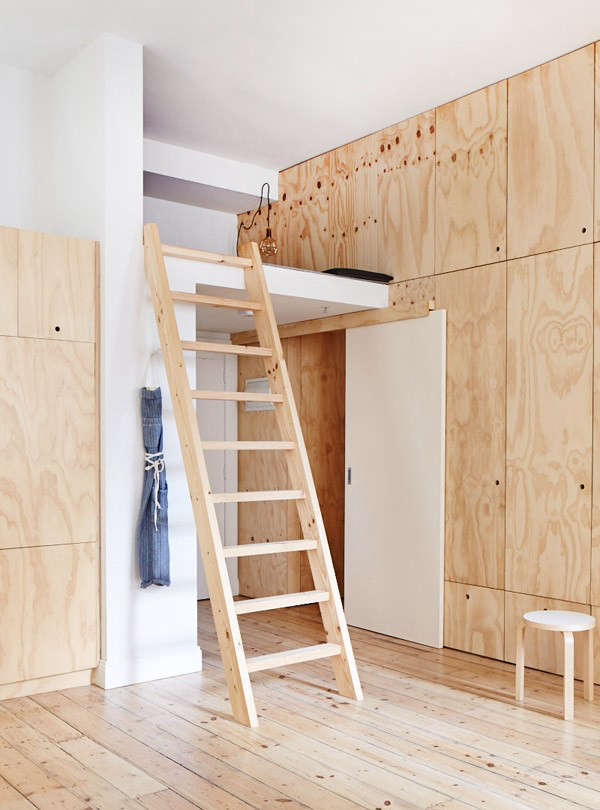 The storage loft bridges the plywood bedrooms box and the bathroom. The white sliding door leads to the child's room, and the front door is situated under the loft.