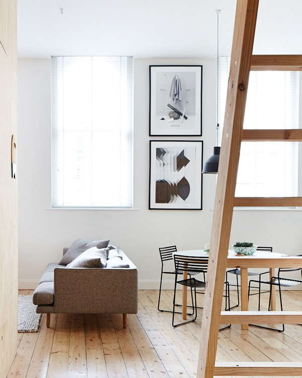 While only 800 square feet, the studio apartment–viewed here from the entry–has tall ceilings and windows on three of its four walls which contribute to the bright, expansive feel of the space. The ladder leads to a storage loft.