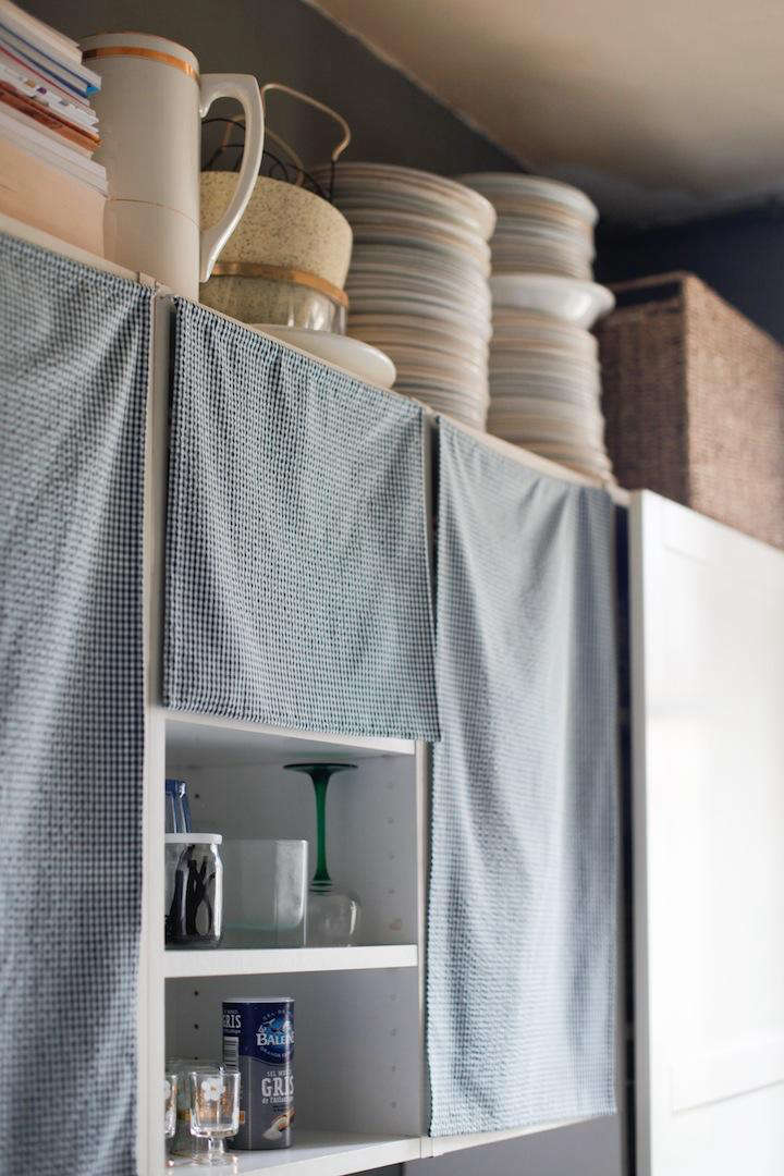 Standard Ikea cabinet doors were taken off and replaced with simple tea towels for more character. SeeDone/Undone with Clarisse Demory in Paris. PhotographbyNatalie Weissfor Remodelista.