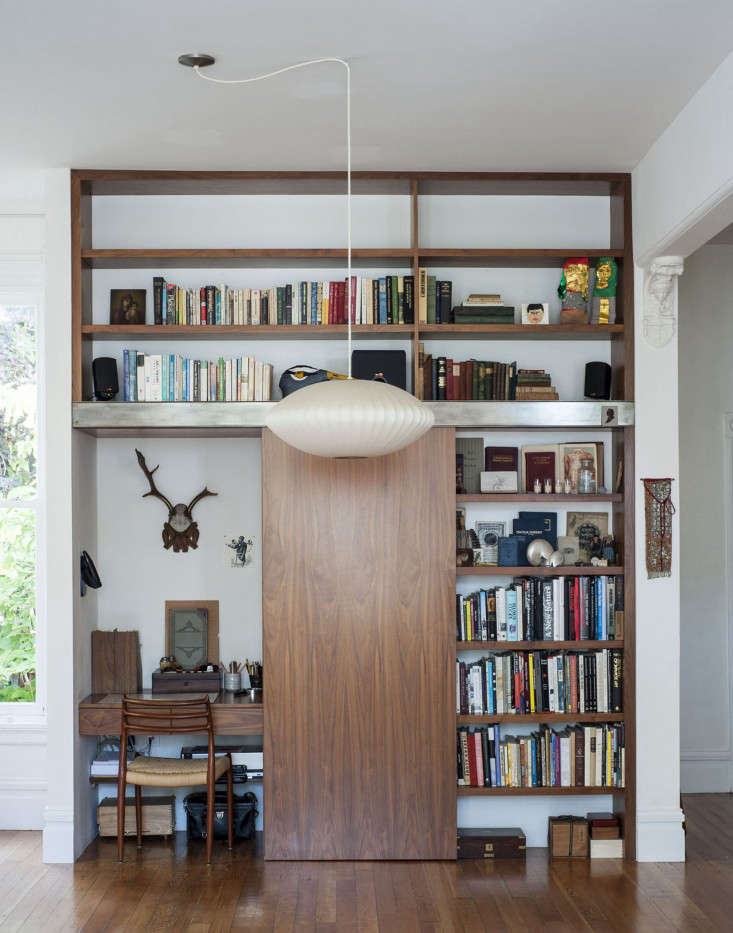 In Dagmar Daley and Zak Conway's San Francisco Victorian, a shelving unit of their own design features a sliding panel to conceal the desk area. See more of the design at The Disappearing Home Office. Photograph byMatthew Williamsfor Remodelista.