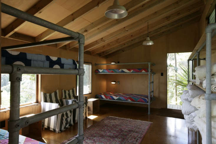 A bunk room with built-in metal piping beds and storage shelves in a New Zealand beach hideaway. PhotographbyPatrick Reynolds,courtesy ofCheshire Architects, fromArchitect Visit: A Kiwi Beach Compound, Cross-Cultural Edition.