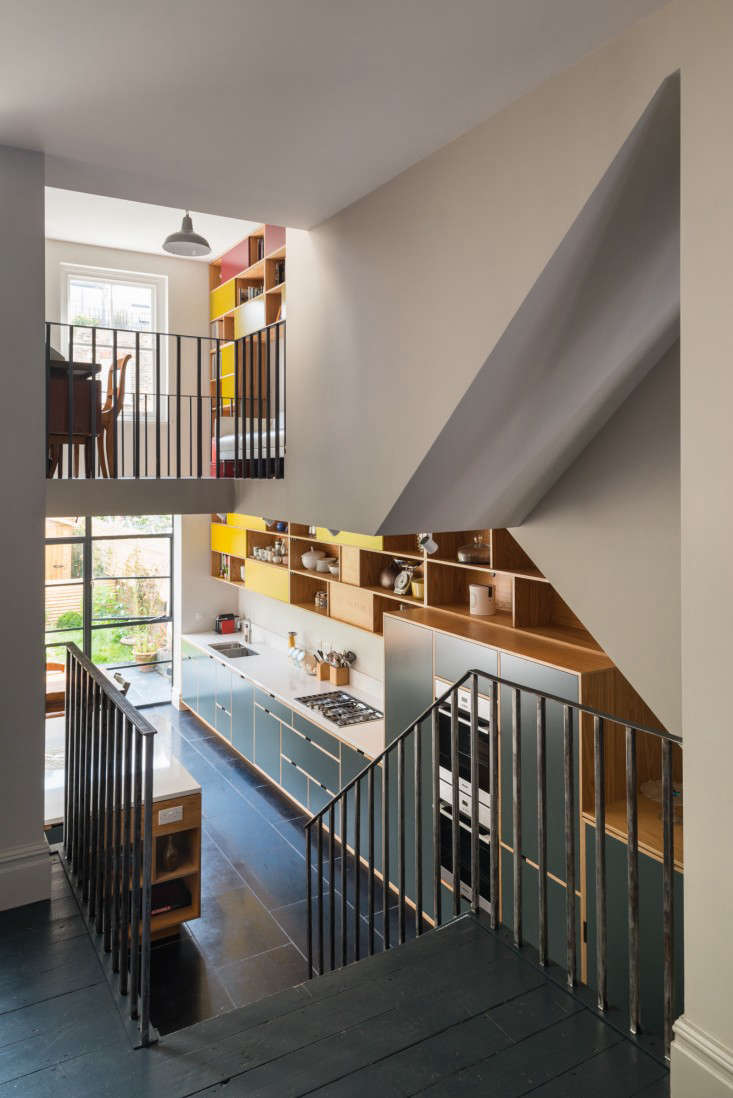 Stairs off the living room lead down to the large kitchen and dining area, which has been opened up in the front and back to the study. The steel banister echoes the lines of the balcony above and the new screen of steel-frame glazing below.