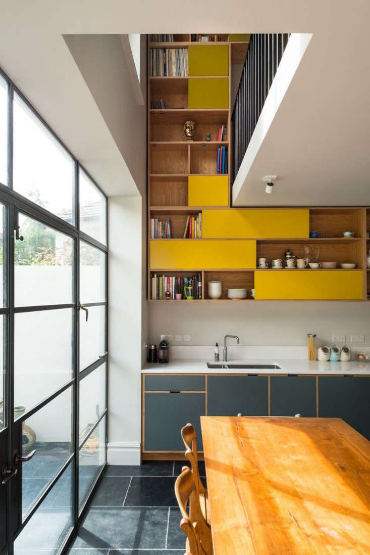 The cabinets are made of oak-veneered birch ply and have spray-lacquered MDF fronts paired with open shelves, a combination that gracefully morphs from kitchen storage to study bookshelves (to differentiate the two spaces, the colors gradually shift).