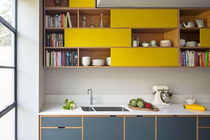 To keep a seamless look, the below-the-counter cabinets have cutout door pulls. The upper cabinets have sliding doors. Photograph by Jocelyn Lowfrom Uncommon Projects.