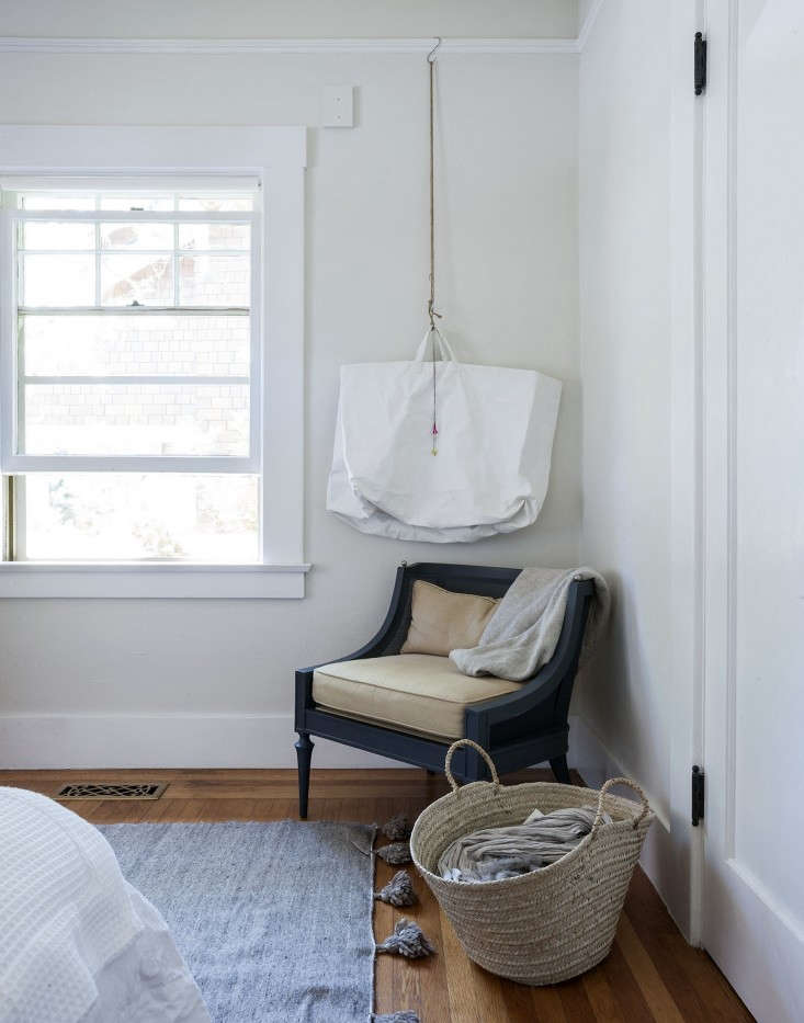 """Picture rail moldings can be used for hanging more than art. """"I used S hooks and a brass ring hung from rope for suspending a white-painted canvas bag where I store off-season scarves,"""" she says in her original post."""