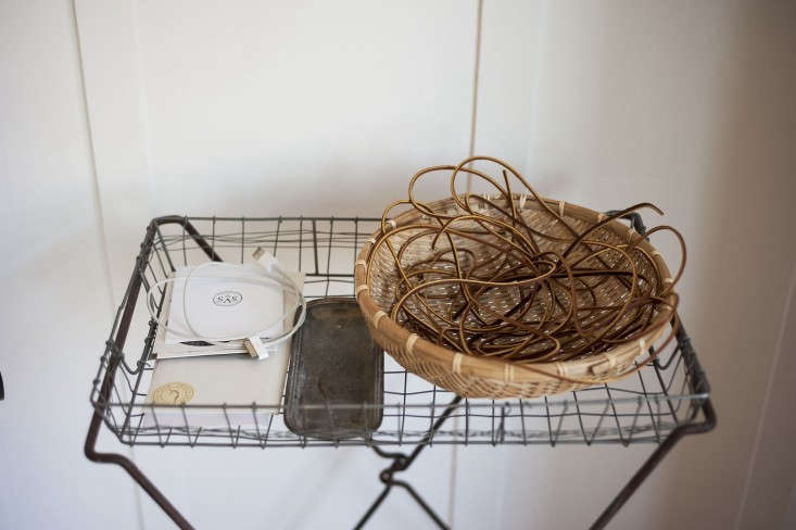 """What is this charming improvised tray table? """"The tray stand is made from a folding laundry basketframepicked up at theAlameda flea market with a wire tray added on top. It's my cell phone charging station and where Iput all my papers before they make it to my office space,"""" explains Sarah."""