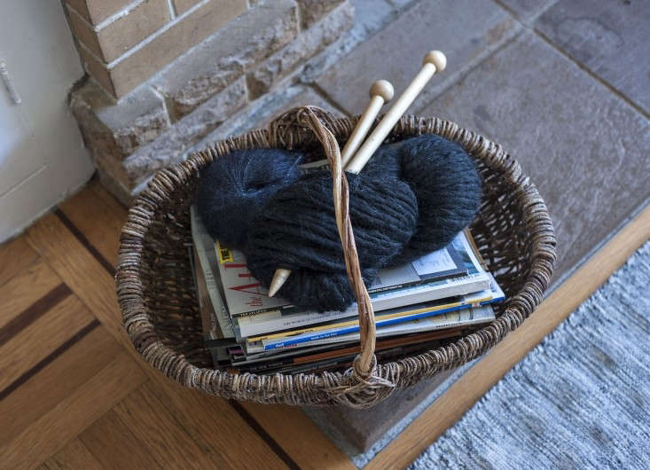 Here, a rustic woven basket contains magazines and a knitting project.