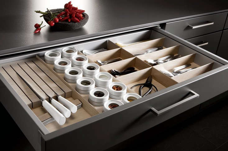 A tailormade storage drawer with sections for knives, flatware, spices and other tools from SieMatic Kitchens.