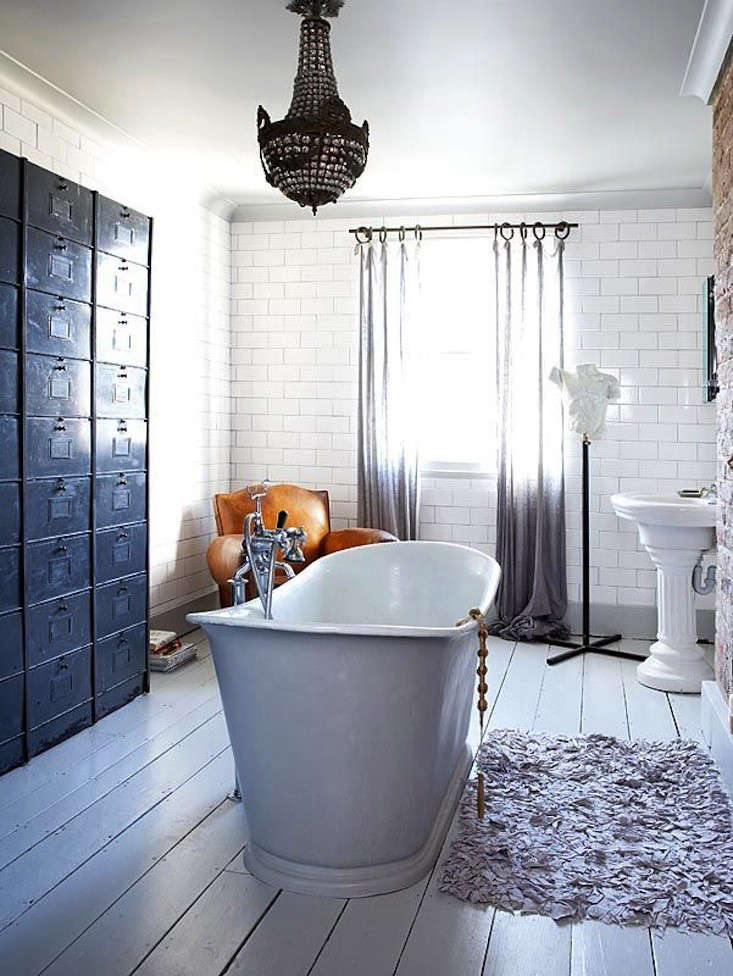 A glamorous bathroom mixes a feminine chandelier with industrial cabinets used for storage. Photographfrom Living Etc. seen on Lovenordic Design.