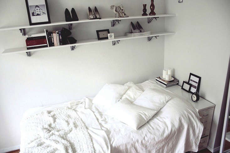 In a small bedroom, a white filing cabinet works as a headboard/bedside table. Photograph via Hananaa.