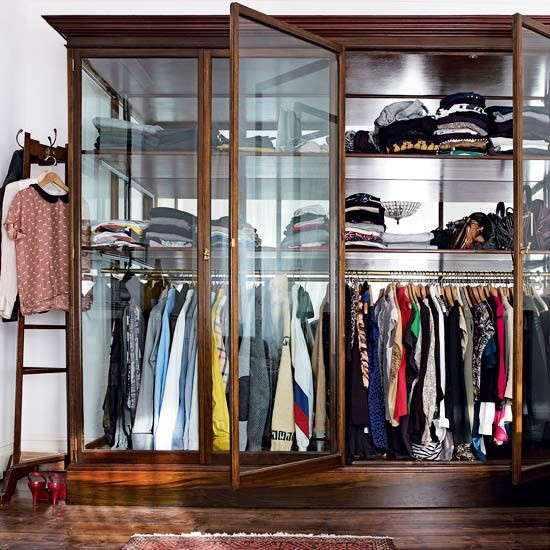 A vintage shop display cabinet repurposed as a glass storage wardrobe. Photograph via House to Home.