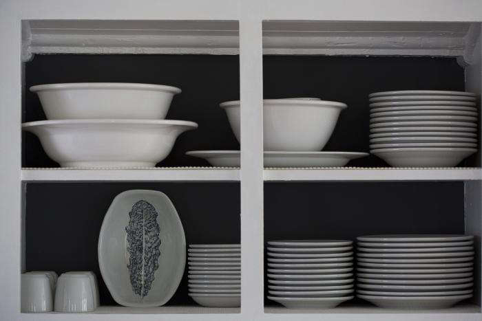 Wendy turned her kitchen shelves into an installation of sorts by painting the frames white and the back wall a custom flat graphite gray, to create contrast for the white dishes on display.