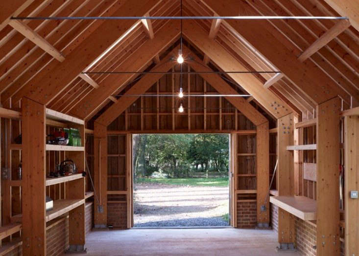 Shelves, storage, and waist-high work stations are built into the walls of this multi-use studio. Photograph via Cassion Castle Architects, from Outbuilding of the Week: Designer Tim Lloyd's Timber Work Studio in Hampshire.