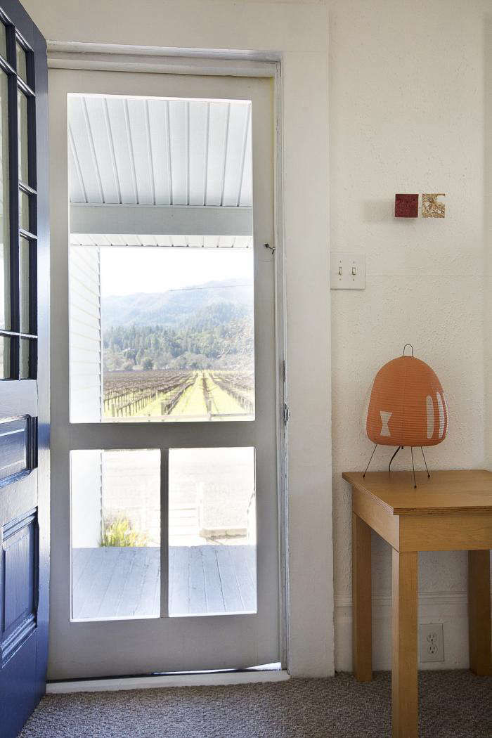 A screen door with a view of the vineyards. A Noguchi Lamp sits on a Roy McMakin wooden table.
