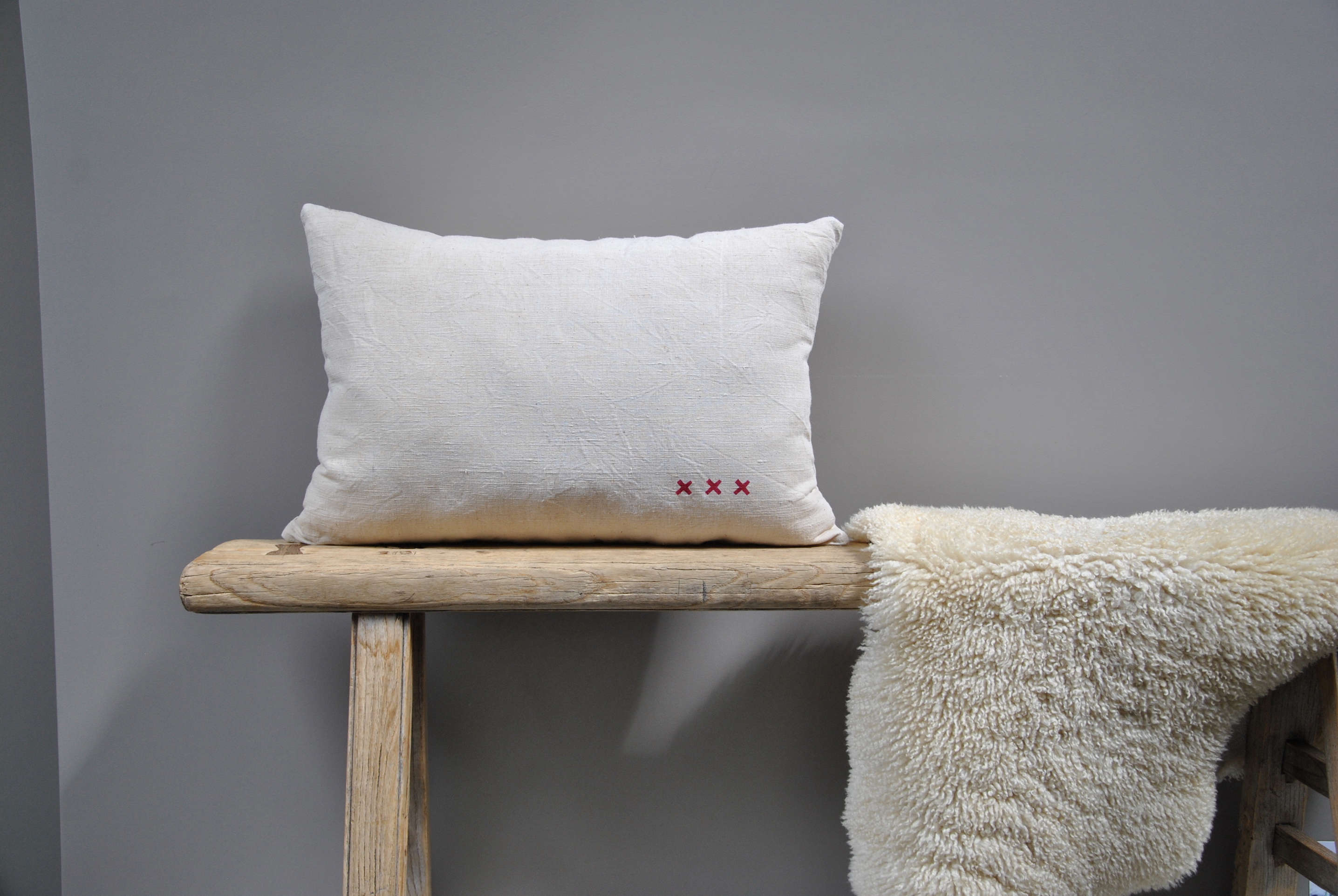 Pillow of vintage linen with X-stamp decoration from Le Reperes des Belettes | Remodelista