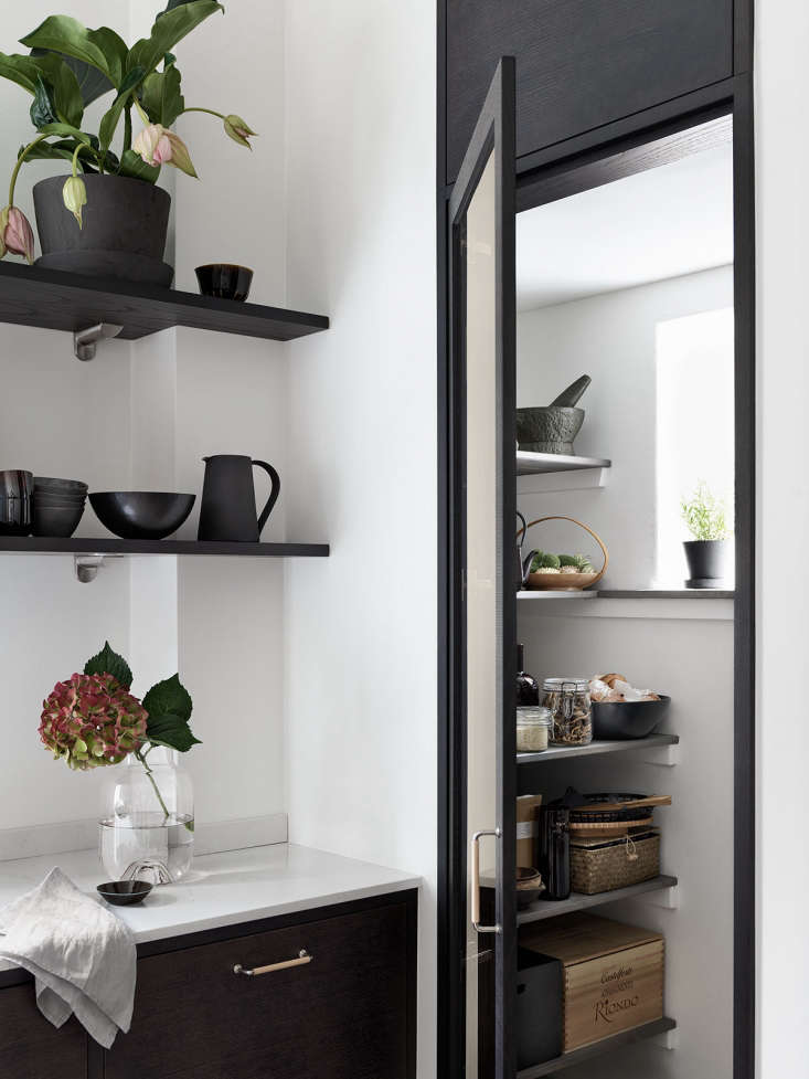 """In the """"Bistro"""" kitchen by Swedish firmBallingslöv, dark gray shelves hold the essentials behind a glass-fronted corner cabinet. See the rest inKitchen of the Week: A Swedish Kitchen with a Place for Everything. Photograph courtesy of Ballingslöv."""