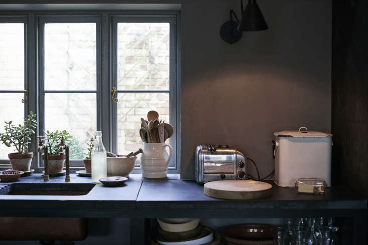 A vintage enamel bread box, glass butter dish, and ceramic jug holding wooden spoons up the charm factor. The counters, by the way, are made of slate reclaimed from an old billiards table.