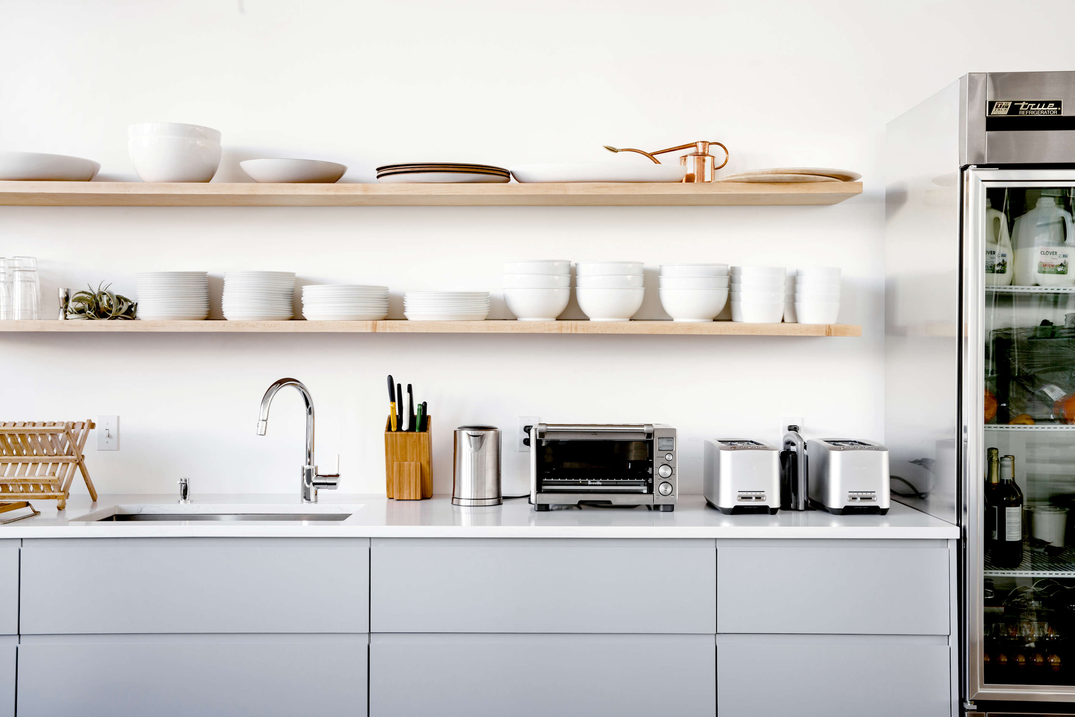 Gray kitchen cabinets in Everlane's lofty white office in SF, Carlos Chavarría photo | Remodelista