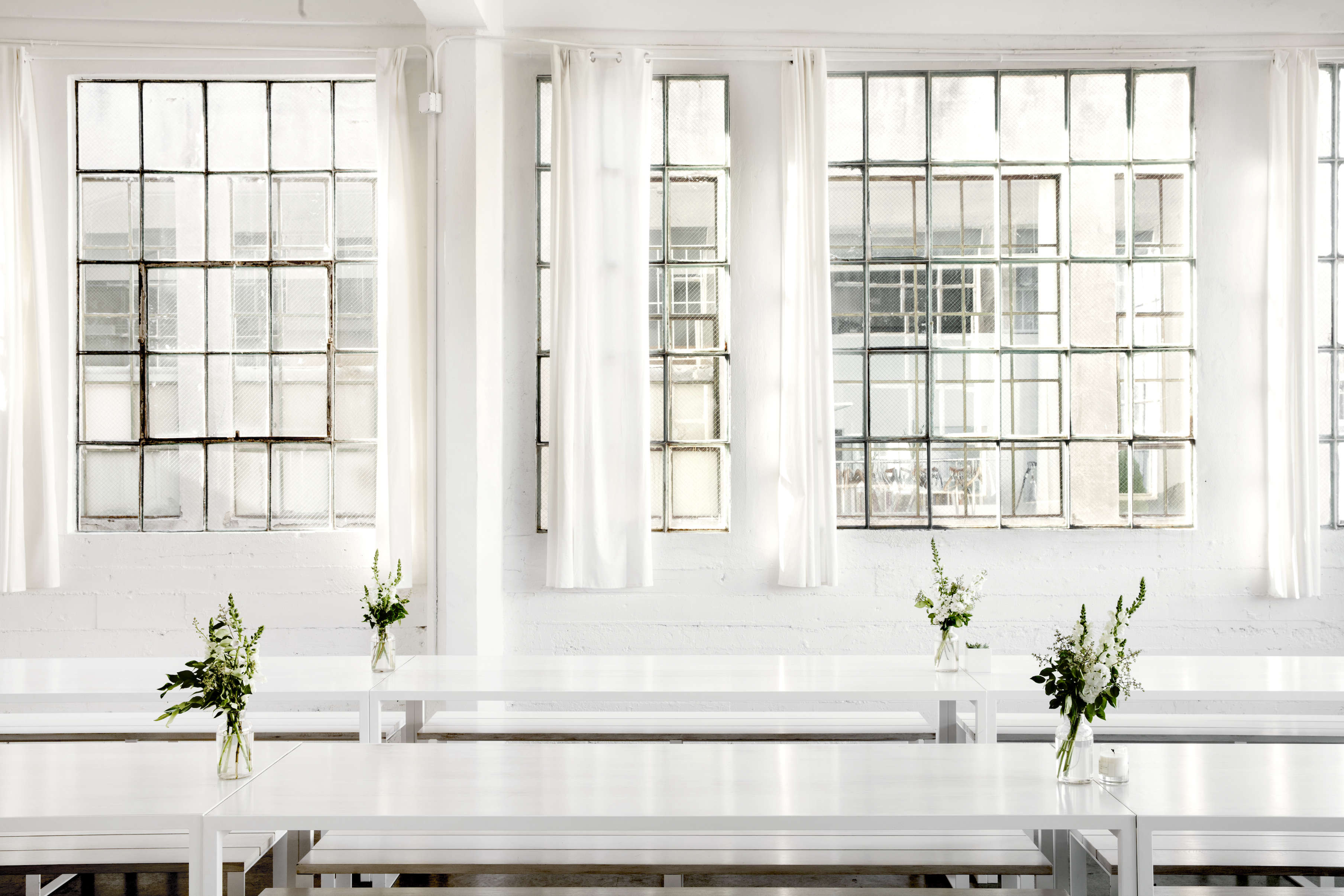 White picnic tables by Ohio Design in Everlane's lofty white office in SF, Carlos Chavarría photo | Remodelista
