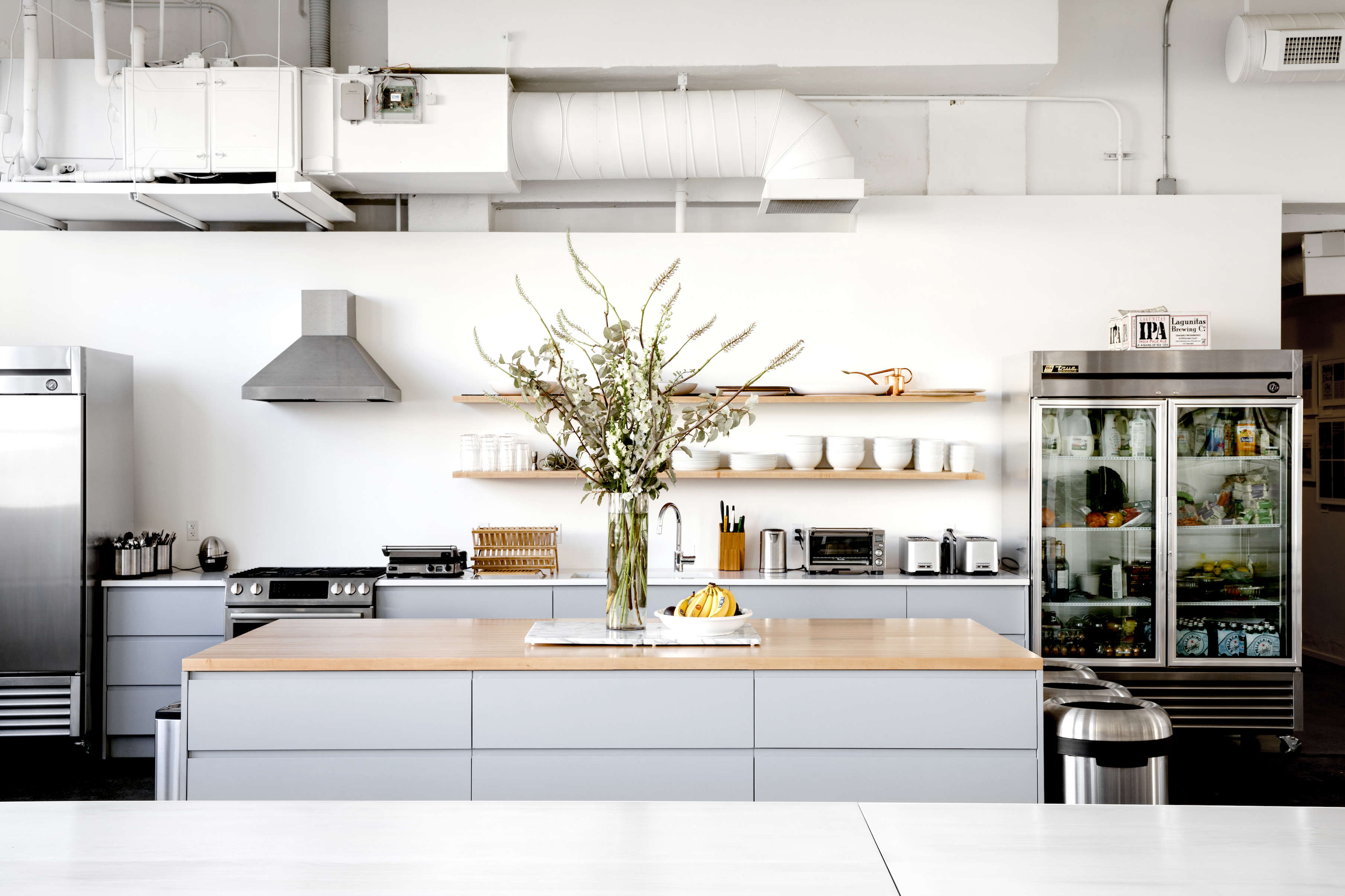 Open kitchen with island in Everlane's lofty white office in SF, Carlos Chavarría photo | Remodelista