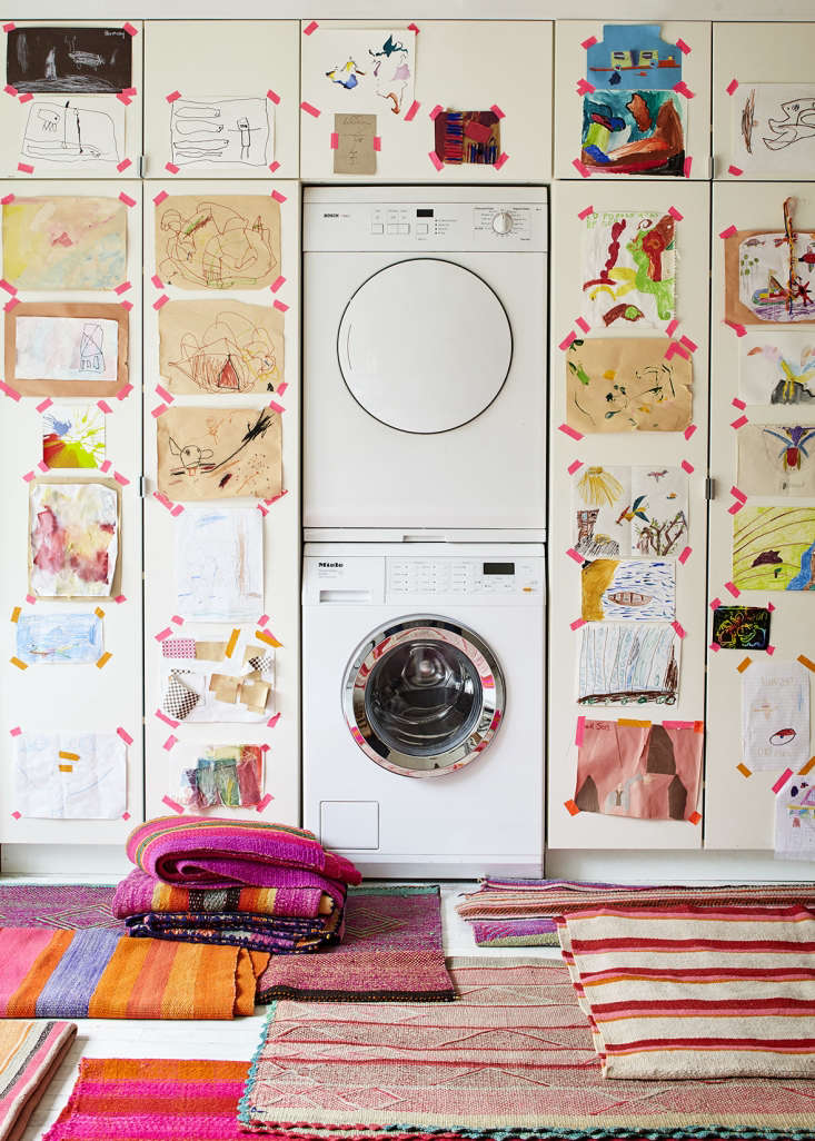 A wall of Ikea cabinetry surrounding a stacked washer/dryer unit has the look of custom built-ins in this laundry area. PhotographbyDana Gallagher, styling byHelen Crowther, from Embrace the Bright: A Textile Shop Owner at Home in Brooklyn.