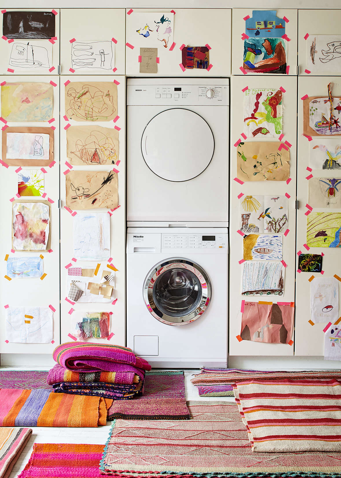 A washer and dryer, both in white, are camouflaged among white Ikea kitchen cabinets. Photograph by Dana Gallagher and styling by Helen Crowther, from Embrace the Bright: A Textile Shop Owner at Home in Brooklyn.