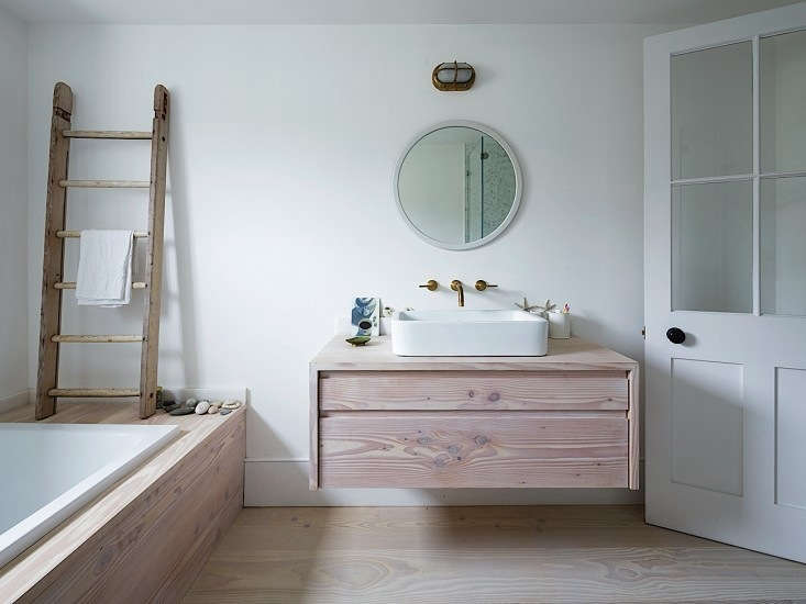 A vanity that has it both ways—ample storage and an airy feel. Photograph courtesy of Rory Gardiner, from Steal This Look: A London Bathroom Clad in Dinesen Wood.