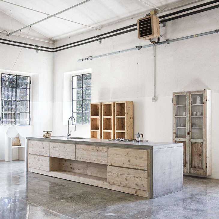 Ashow kitchen in a rescued spinning mill in northern Italy features ground concrete floors and reclaimed shelving; seeA Showroom in Italy Where Everything Is Made from Salvaged Materials.