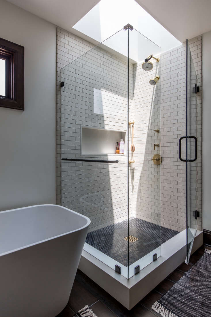 Another one, similarly shaped, in a glass-walled shower crowned by a skylight.Photograph byLaure Joliet, courtesy ofBrian Paquette Interiors, fromBungalow Upgrade: A Craftsman House Orchestrated for a Hollywood Composer.