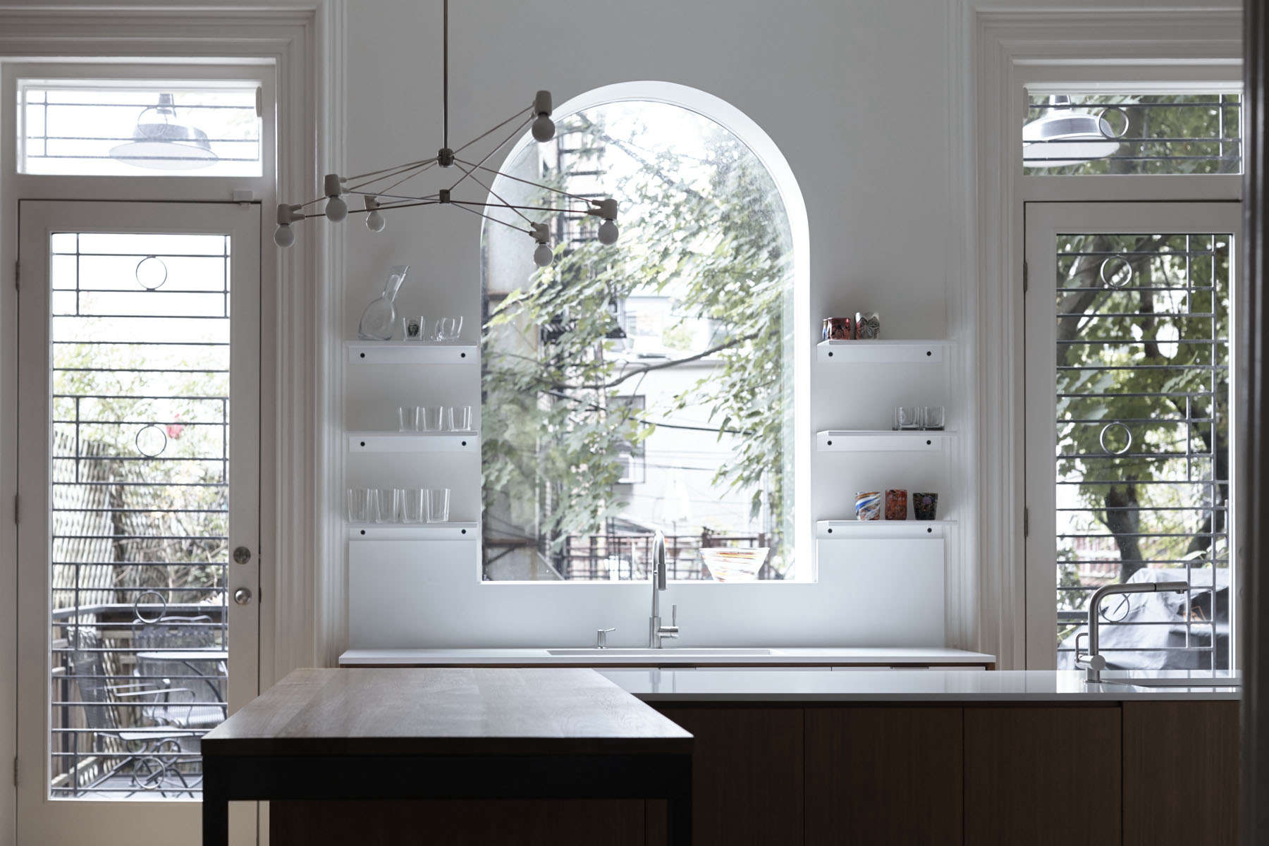 Large arched window and glass-paneled door and windows in a Brooklyn kitchen remodel by architect Shauna McManus